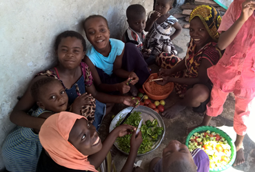 Children in Jambiani chopping vegtables on a food travel zanzibar